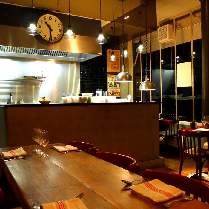 La salle du restaurant et la cuisine ouverte